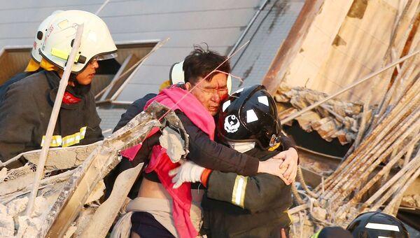 Спасатели помогают мужчине, пострдавшему во время землетрясения на Тайване, 6 февраля 2016