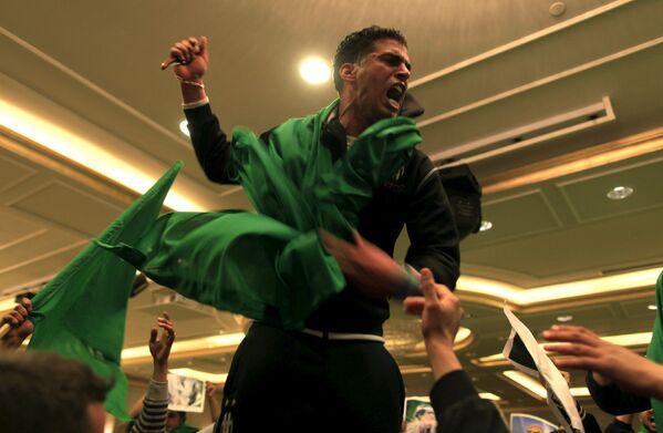 Сторонник ливийского лидера Муаммара Каддафи во время протестов в Триполи, Ливия. Март 2011