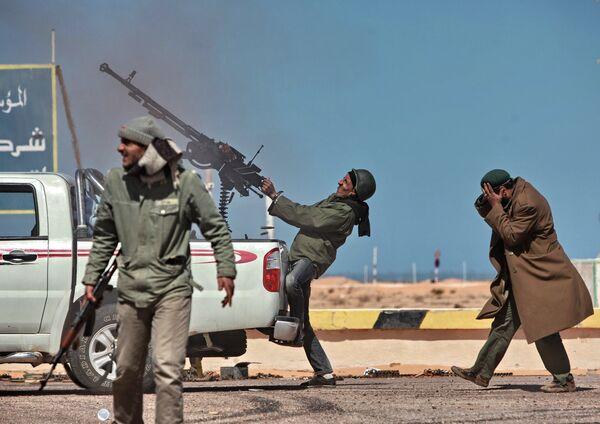 Боец оппозиции стреляет из пулемета по истребителю в городе Рас-Лануф, Ливия. Март 2011