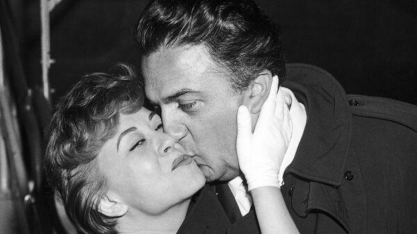 Итальянский кинорежиссер Федерико Феллини с женой актрисой Джульеттой Мазиной во время прибытия на Международный кинофестиваль в Берлине, 27 июня 1958