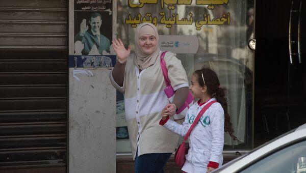 Женщина с ребенком на одной из улиц Дамаска в первый день перемирия