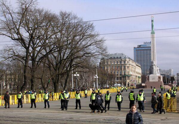 Сотрудники полиции стоят в оцеплении на площади перед памятником Отечеству и свободе в Риге - конечной точке маршрута шествия латышского легиона Ваффен СС