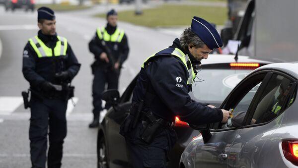 Полицейские досматривают автомобиль на подъезде к аэропорту в Брюсселе. Архивное фото