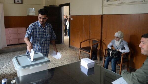Мужчина опускает конверт с бюллетенем в урну на одном из избирательных участков во время голосования на парламентских выборов в Сирии. Архивное фото