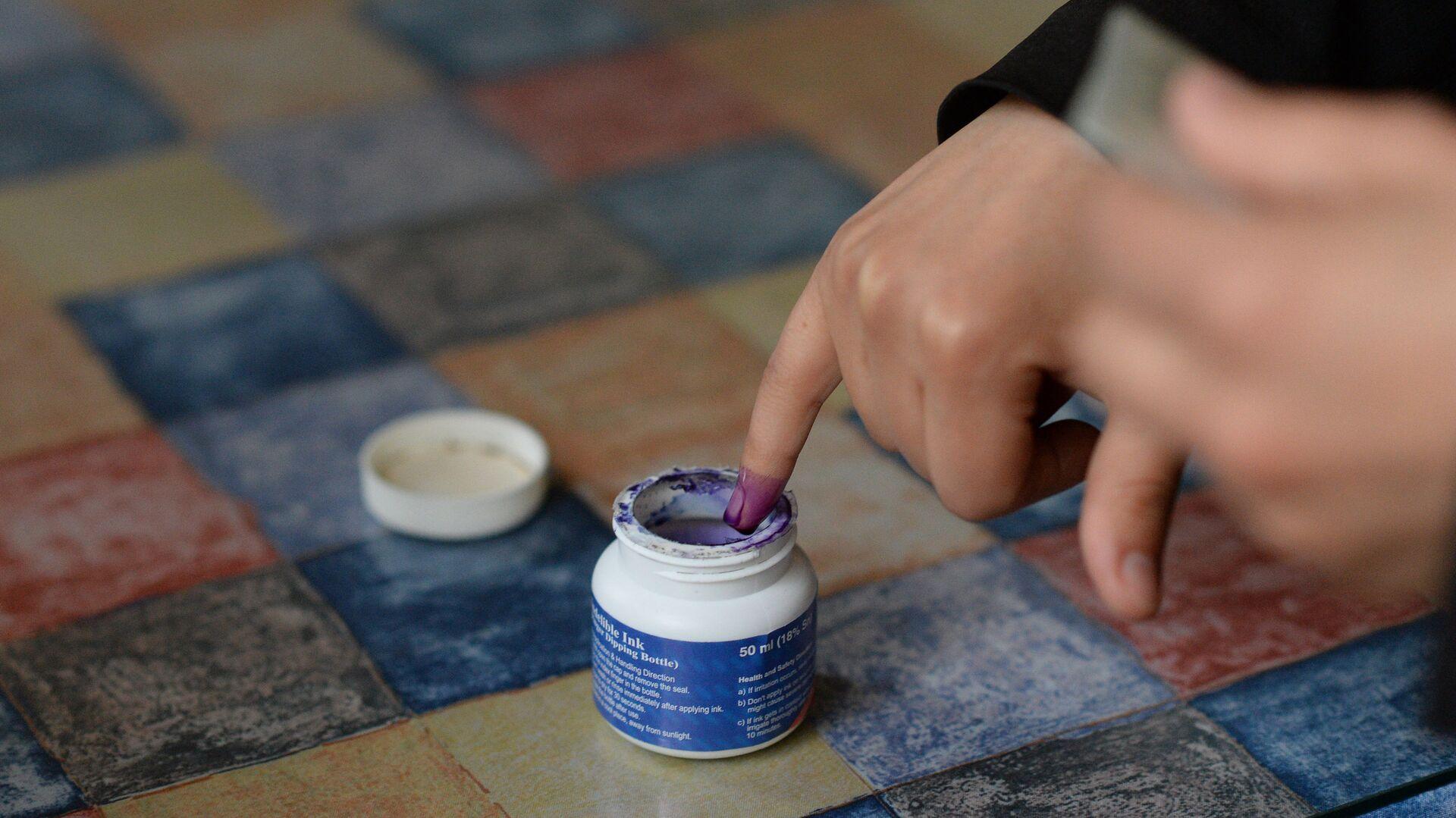 Женщина опускает палец в емкость с чернилами для отметки в списке избирателей во время голосования на парламентских выборов в Сирии - РИА Новости, 1920, 03.05.2021