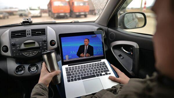 Пассажир смотрит трансляцию ежегодной специальной программы Прямая линия с Владимиром Путиным на автомобильной стоянке в Новосибирской области