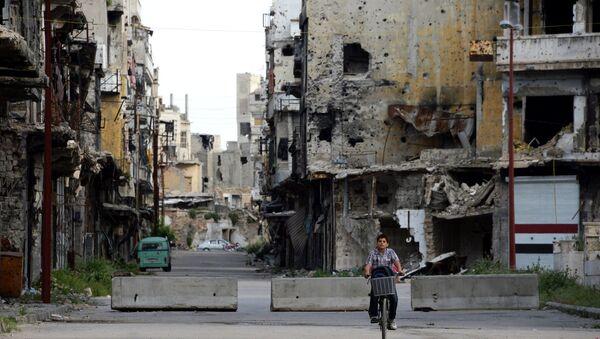 Мальчик едет на велосипеде по одной из улиц в Хомсе. Архивное фото