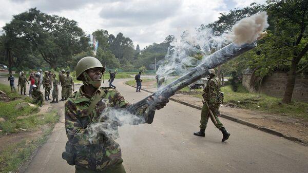 Сотрудник полиции выпускает слезоточивый газ, Найроби, Кения