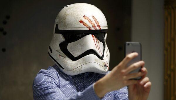 Журналист делает селфи в маске, произведенной в студии Pinewood Studios в Англии