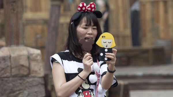 Посетительница первого на территории континентального Китая парка развлечений Диснейленд в Шанхае ест мороженое в виде Микки Мауса
