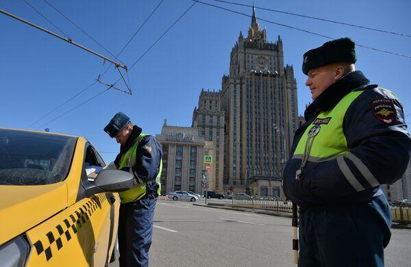 Сотрудники ГИБДД проверяют документы у водителя в рамках рейда против нелегальных таксистов в Москве