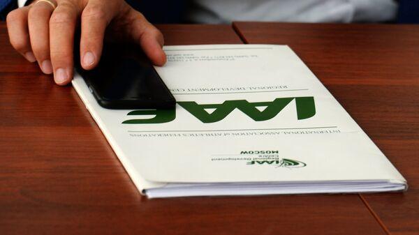 Папка с символикой IAAF на столе перед участником пресс-конференции представителей Всероссийской федерации легкой атлетики в Чебоксарах