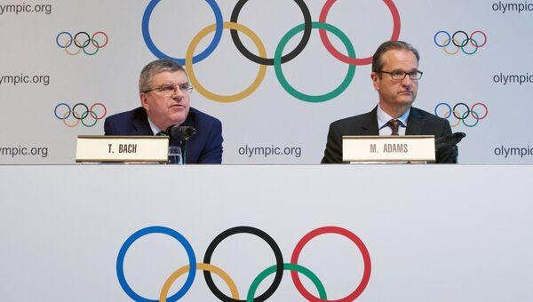 Президент МОК Томас Бах и директор по коммуникациям Марк Адамс на пресс-конференции по итогам специального заседания Международного олимпийского комитета в Лозанне. 21 июня 2016