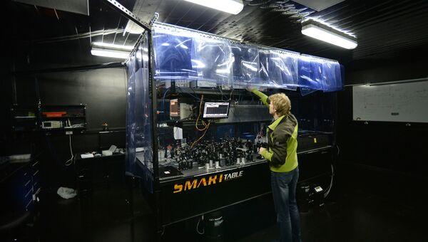 Научный сотрудник в Российском квантовом центре производит юстировку оптической схемы на установке по исследованию свойств квантового света