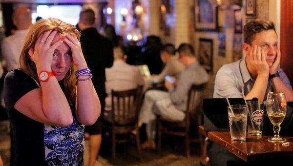 Люди смотрят трансляцию результатов референдума в одном из пабов Нью-Йорка