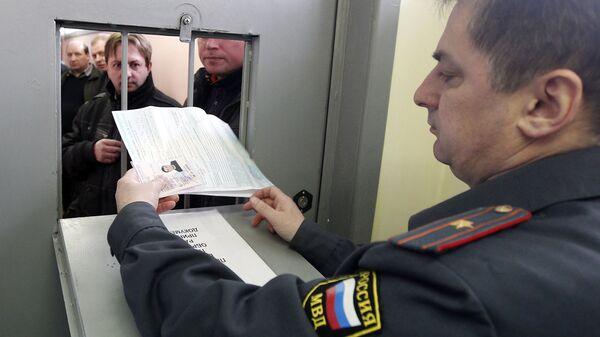 Инспектор ГИБДД принимает документы от водителя