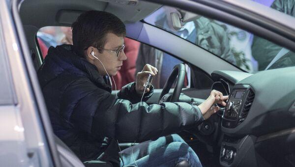 Посетитель осматривает салон автомобиля Lada Vesta после начала продаж в Москве