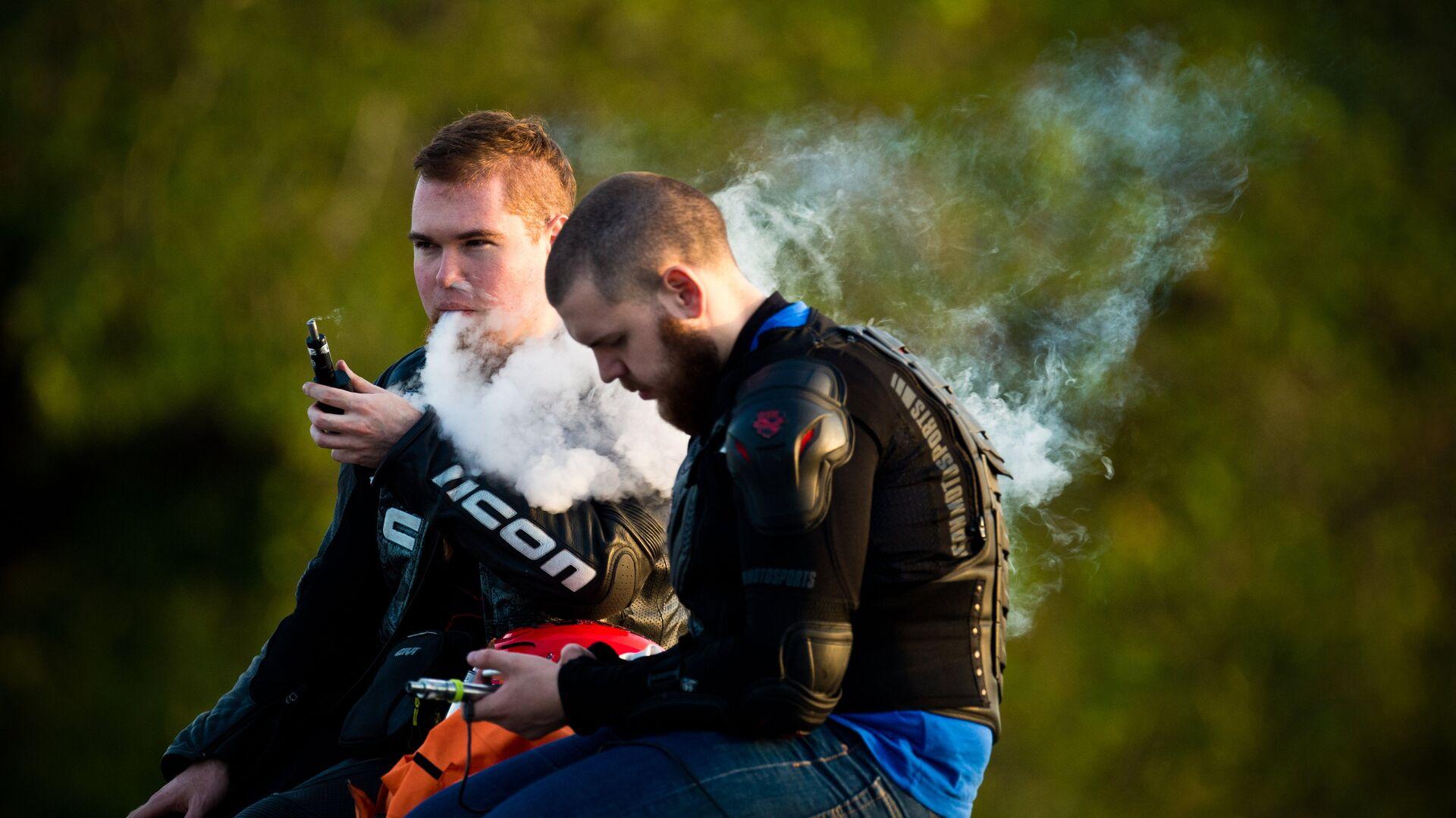 Молодые люди курят электронные сигареты на смотровой площадке Воробьевых гор в Москве - РИА Новости, 1920, 23.07.2021