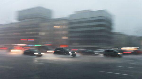 Автомобили едут по Зубовскому бульвару в Москве во время сильного дождя