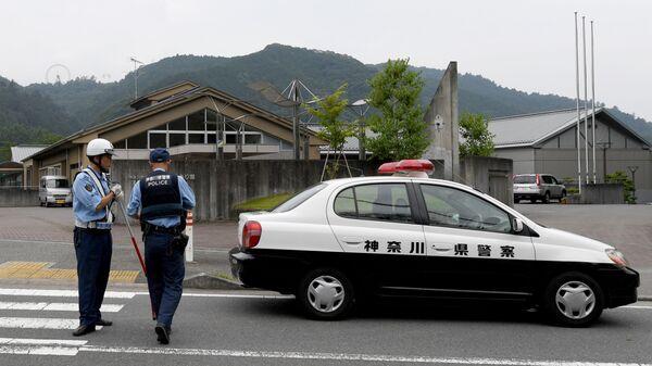 Сотрудники правоохранительных органов Японии рядом с интернатом для инвалидов Сад лилий в Цукуи под Токио. 26 июля 2016