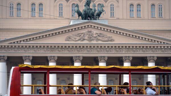 Туристы проезжают на экскурсионном автобусе мимо Большого театра в Москве. Архивное фото