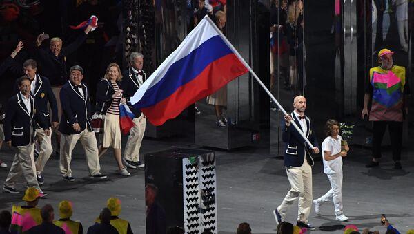 Знаменосец сборной России Сергей Тетюхин несет российский флаг на церемонии открытия летних Олимпийских игр в Рио