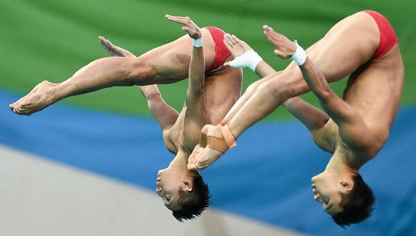 Чэнь Айсень и Линь Юэ (КНР) во время финальных соревнований по синхронным прыжкам с вышки 10 м среди мужчин на XXXI летних Олимпийских играх