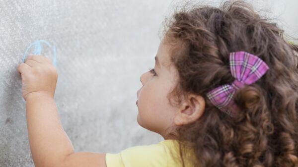 Девочка рисует левой рукой