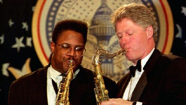 Президент США Билл Клинтон играет на саксофоне вместе с музыкантом Джо Хендерсон в Арканзасе во время бала состоявшегося после его инаугурации