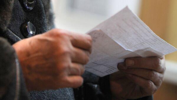 Женщина проверяет правильность заполнения квитанций об оплате коммунальных услуг. Архивное фото