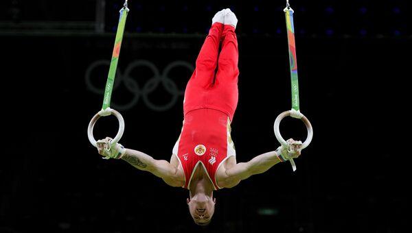 Российский гимнаст Денис Аблязин выполняет упражнения на кольцах на XXXI летних Олимпийских играх