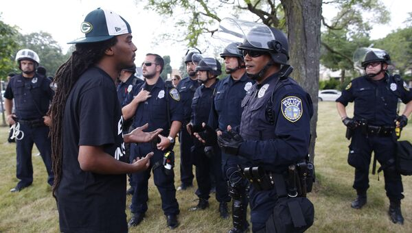 Полицейские и протестующий во время беспорядков в Милуоки. 15 августа 2016