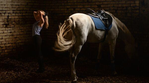 Спортсменка после тренировки со своей лошадью