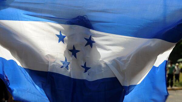 Мужчина держит флаг Гондураса