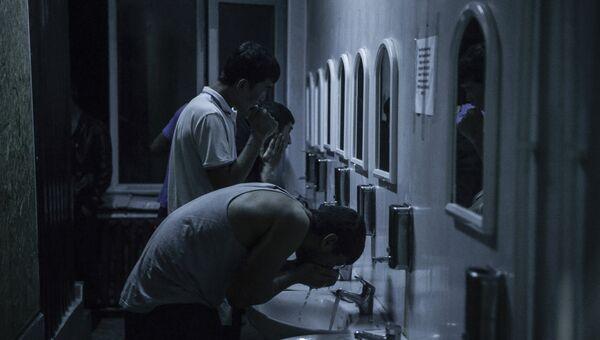 Иностранные рабочие умываются в общежитии для мигрантов в Москве. Архивное фото