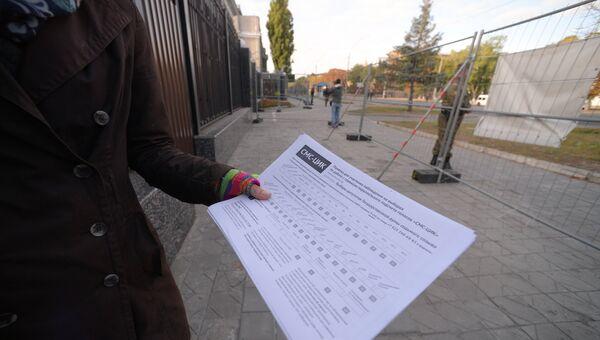 Женщина демонстрирует памятку для наблюдателя на выборах у посольства Российской Федерации в Киеве