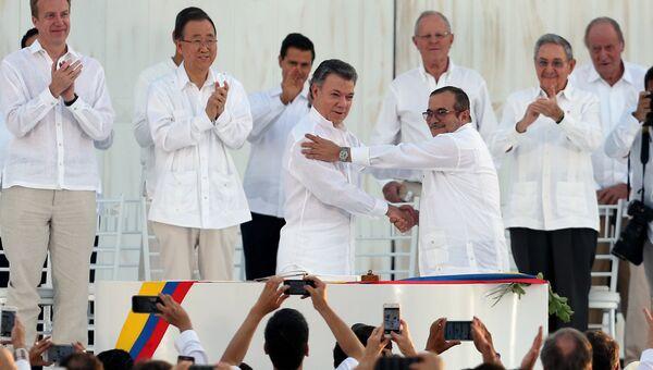 Президент Колумбии Хуан Мануэль Сантос и лидер бывших повстанцев Родриго Лондоньо Эчеверри после подписания соглашения о мире в городе Картахена, Колумбия. 26 сентября 2016