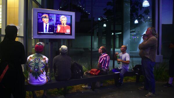Люди смотрят трансляцию дебатов между Дональдом Трампом и Хиллари Клинтон