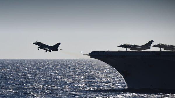 Истребители Rafale взлетают с палубы французского авианосца Шарль де Голль в Средиземном море. 29 сентября 2016