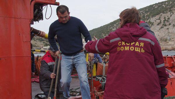 Сотрудница скорой помощи встречает одного из спасенных членов экипажа плавучего крана, затонувшего у берегов Крыма, в порту Балаклавы