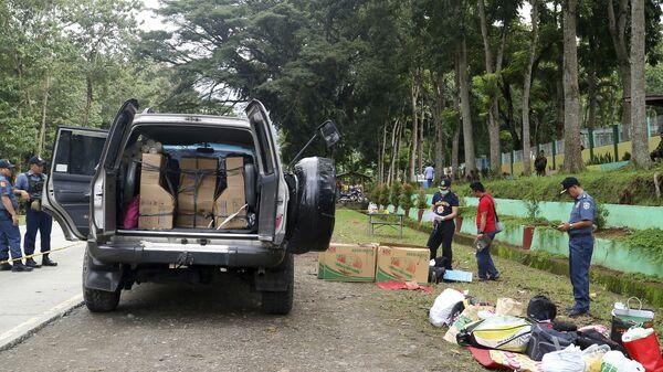 Сотрудники полиции проводят досмотр автомобилей в рамках антинаркотического рейда в городе Макилала, Филиппины