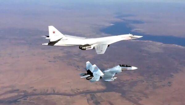 Истребитель Су-30СМ и бомбардировщик-ракетоносец Ту-160 ВКС РФ во время боевого вылета в Сирии. Архивное фото