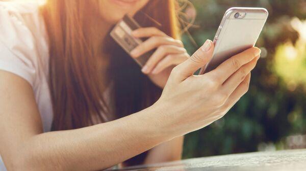 Девушка совершает покупки при помощи мобильного телефона