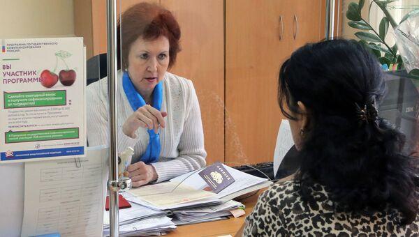 Сотрудница обслуживает клиента в в пенсионном фонде. Архивное фото