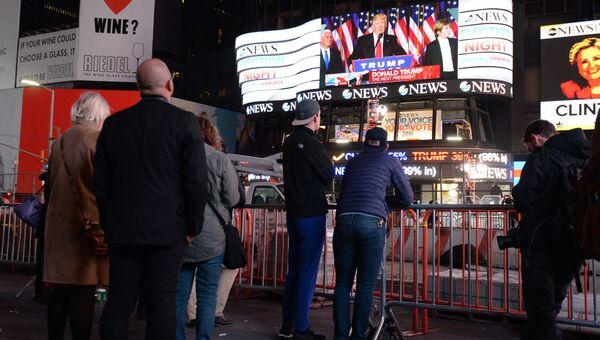 Горожане на площади Таймс-сквер в Нью-Йорке смотрят трансляцию выступления избранного президента США Дональда Трампа