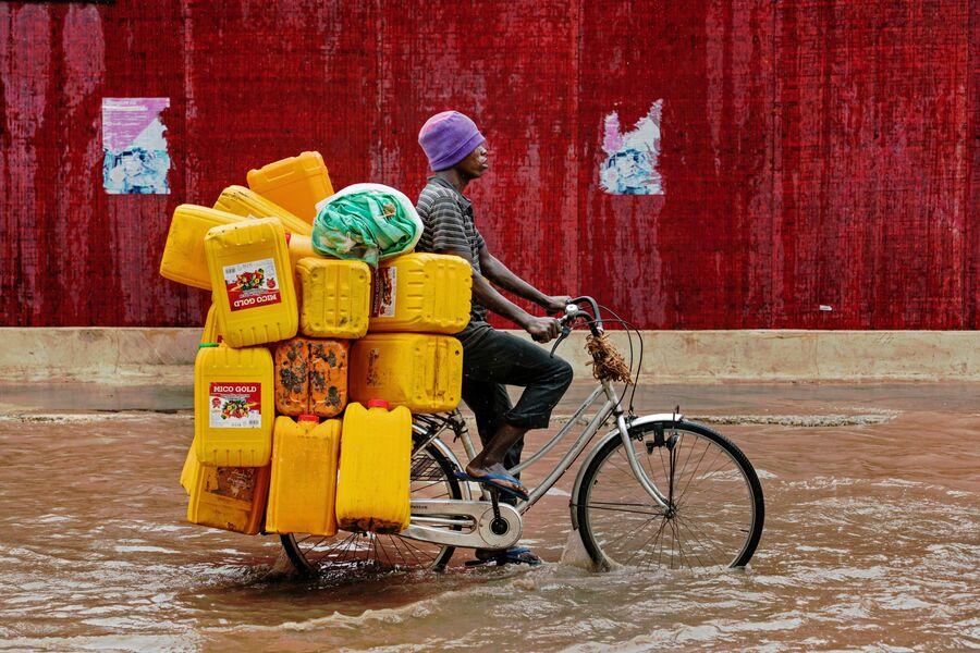 Велосипедист на затопленной улице в городе Дар-эс-Салам, Танзания