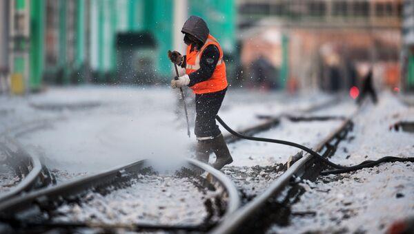 Рабочий очищает железнодорожный путь, архивное фото