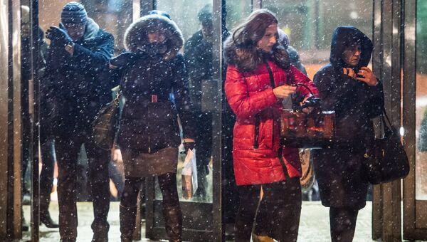 Люди выходят со станции метро Новокосино в Москве во время снегопада