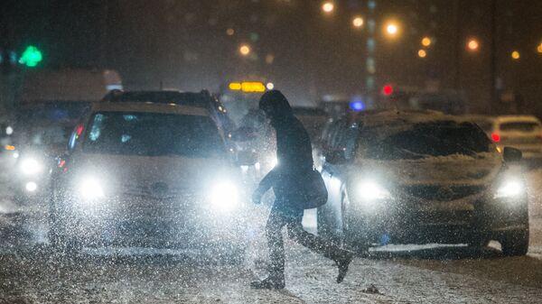 Прохожий переходит дорогу в Москве во время снегопада. Архивное фото