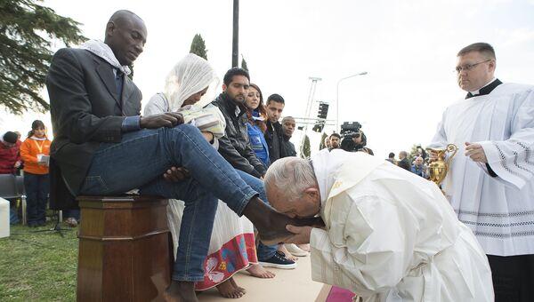 Папа Римский Франциск во время омовения ног мигрантам в центре для беженцев . Архивное фото